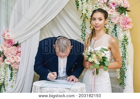 Wedding ceremony. The bride and groom leaving their signatures