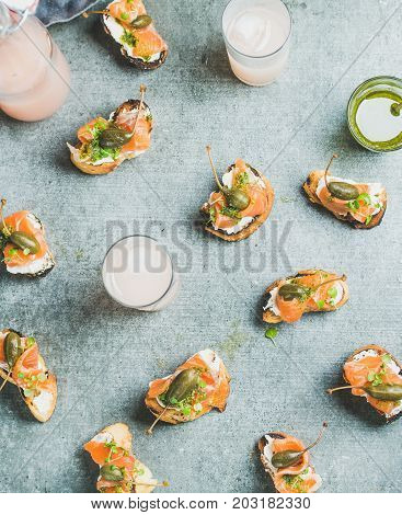 Crostini with smoked salmon, pesto sauce, watercress and capers and pink grapefruit cocktails over grey background, top view, flay-lay. Party, catering or fingerfood concept