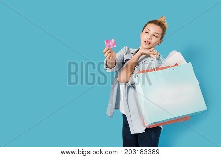 Satisfied woman with shopping bags and card in hand