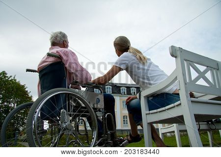 Young woman daughter with senior father in wheelchair at nursing retirement home, Copenhagen, May 25, 2010