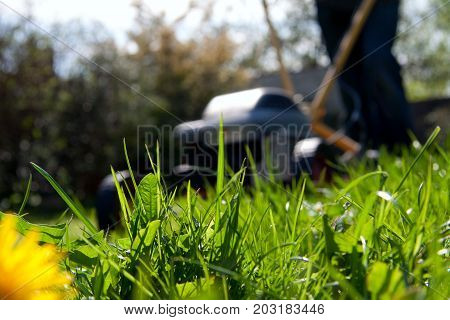 Blurred person mowing the lawn with a lawn mover