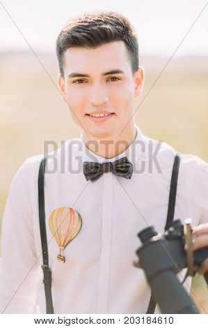 The close-up vertical portrait of the smiling groom in the white shirt decorated wth air-balloon and the bow-tie holding the binoculars