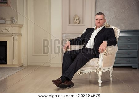 imposing man is sitting in a white chair at the vintage interior. Studio shoot