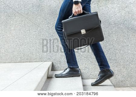 Businessman With Briefcase In Hand Walking Up On Stairs.