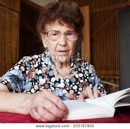 Elderly female at home. Old woman reading book.