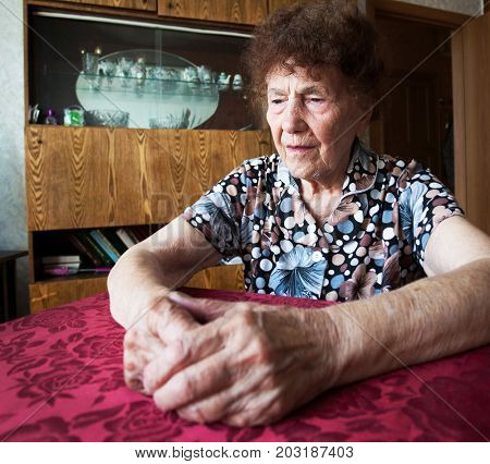 Elderly sad female at home. Old woman.