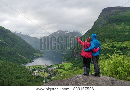 View of the tourist village Geiranger, Norway. Tourists stand at a panoramic point and look at Geirangerfjord and the mountains