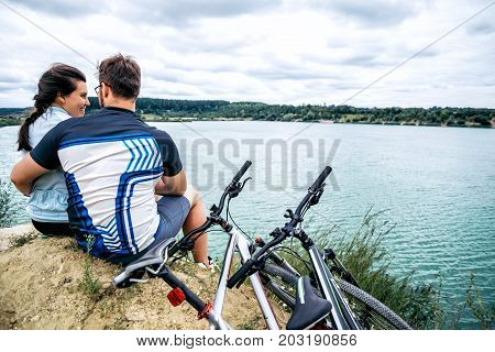 couple sits and looking at the lake two bicycles near them zure water on background