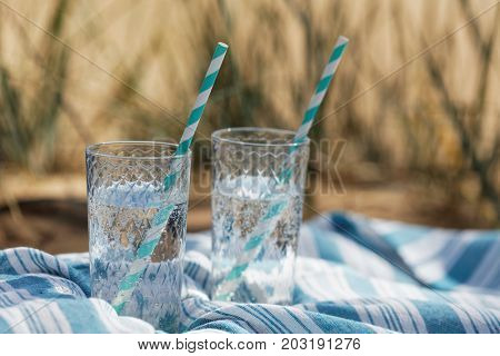 Two glasses of drinks with drinking straw on a beach