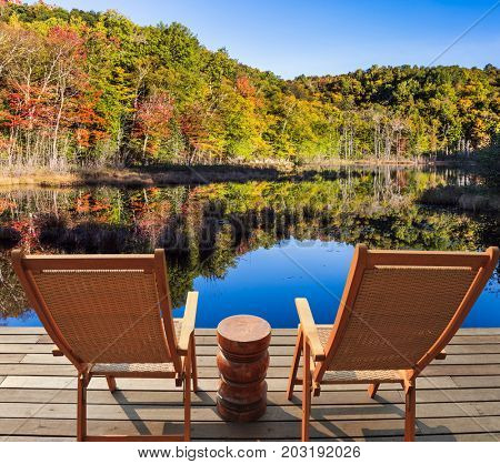 Wooden comfortable loungers on the shore of the pond. Magnificent resort in French Canada - Mont Tremblant. Foliage of forests is reflected in the pond. Concept of ecological tourism