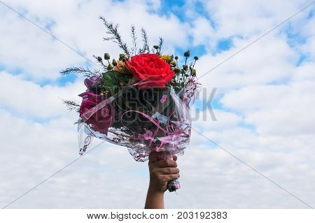 A Bouquet Of Flowers In Hand On Blue Sky Background.
