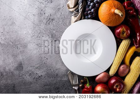 Seasonal Harvest Autumn Concept. Empty Plate with Tasty appetizing fresh autumn seasonal vegetables fruits on grey background top view above copy space