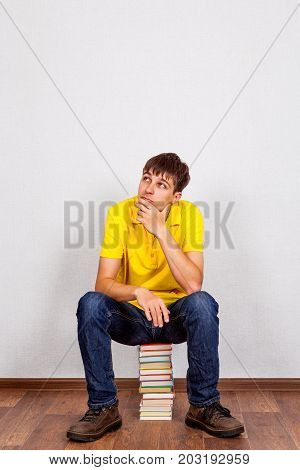 Pensive Young Man with a Books on the Floor in the Room