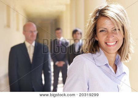 confident happy  businesswoman with her team behind her