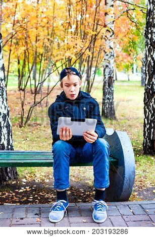 Surprised Teenager with Tablet Computer in the Autumn Park