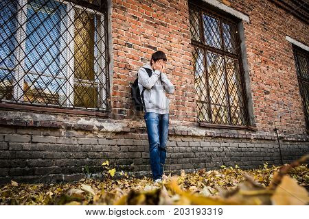 Sad Teenager stand near the Brick Wall of the Old House