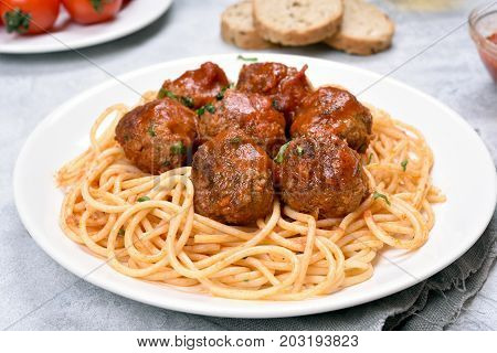 Spaghetti with tomato sauce and meatballs on plate close up view