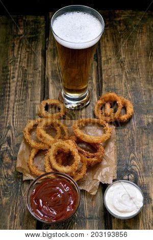 Crispy fried onion rings with sauce and glass of beer