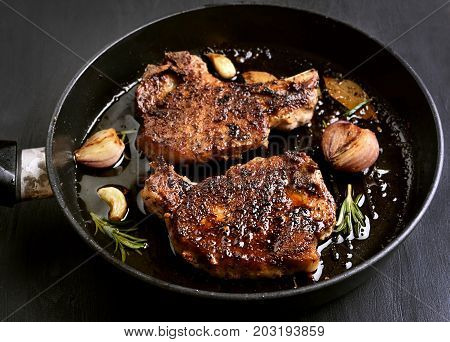 Grilled pork steak in frying pan close up view