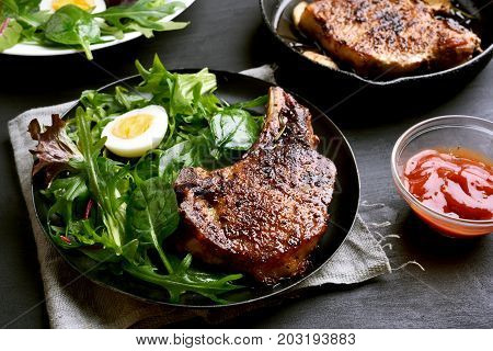Pork steak and salad from green leaves