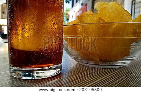 Cola drink and potato chips on a sunny morning
