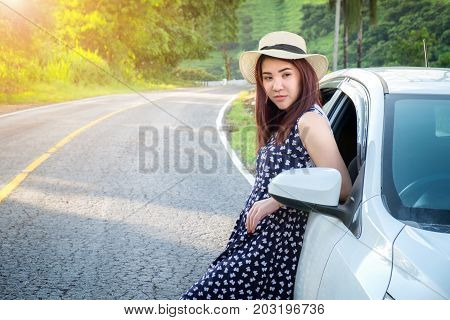 Relaxed happy traveler Young beatiful asian gilr Stand leaning of the car at sunset and beautiful view with mountain road background.