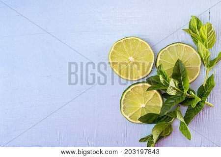 Flat Lay Still Life With Mint And Lime On Blue Background. Pop Art Trend Still Life.
