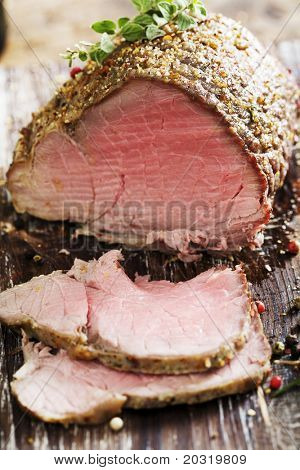 sliced rare beef, roast covered in pepper and herbs