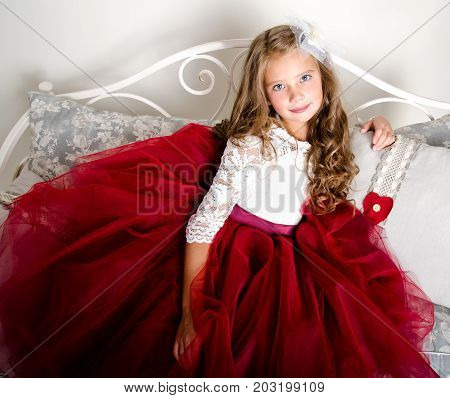 Adorable smiling little girl child in princess dress sitting on the sofa