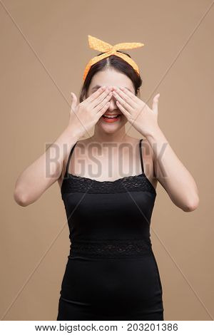 Portrait Of Asian Girl With Pretty Smile In Pinup Style Hiding Eyes By Hand On Yellow Background