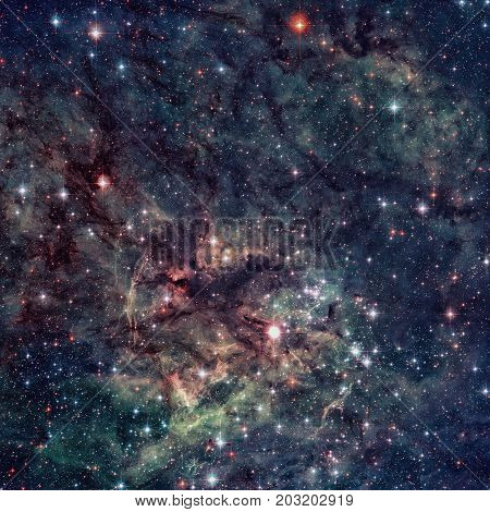 Tarantula Nebula is the star-forming region of ionised hydrogen gas is in the Large Magellanic Cloud, a small galaxy. Retouched image. Elements of this image furnished by NASA.
