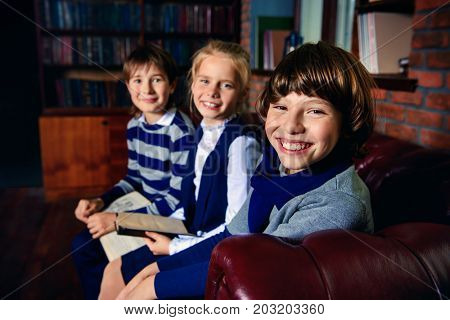 Three joyful children in school clothes sitting on a sofa and reading books. School fashion. Educational concept.