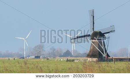 Old Windmill With Modern Windmills In The Background
