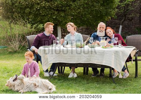 little girl playing with dog while multigeneration family having dinner at backyard