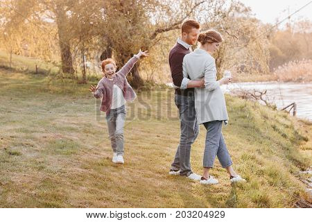 little girl having fun while parents hugging and having conversation together at countryside