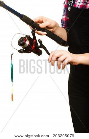 Fishing equipment concept. Woman holding fishing rod with green float. Isolated background.