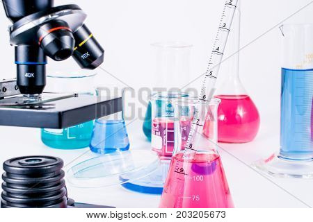 scientist pipetting chemical liquid into flask. Close up of microscope in laboratory and examining samples. laboratory science, clinic and research concept.