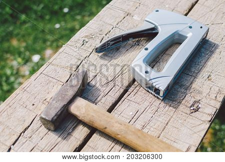 Old hammer and stapler on wood table, photo with selective focus
