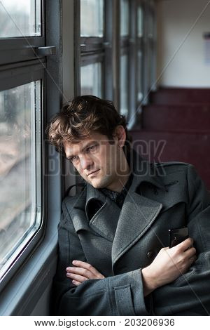Traveling by train. Sad man traveling by train, looking through the window and thinking about unrequited love squeezing the phone in his hand. alone in an empty train wagon. Vertical