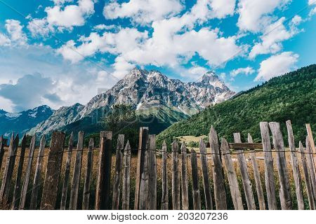 Caucasus mountains behind a wooden fence on the background of the mountain peak Mazeri in Georgia
