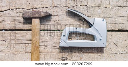 Old hammer and stapler on the wooden table