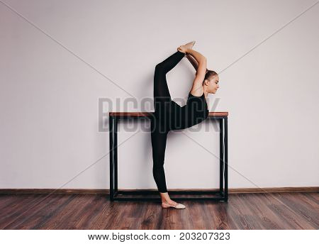 Ballet dancer in black tights on a light background stands near the crossbar. Place for your text.