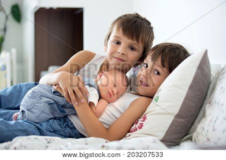 Two Children, Toddler And His Big Brother, Hugging And Kissing Their Newborn Baby Brother