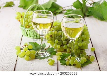 Glasses with white wine and fresh grapes on a white wooden table.
