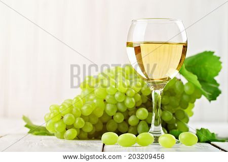 A glass of white wine and fresh grapes on a white wooden table.
