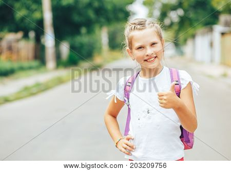 Smiling pretty girl goes to school again.