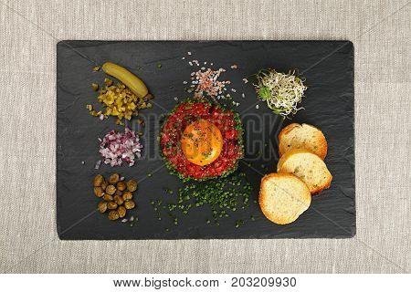 Raw Meat Tartare Steak And Egg Yolk On Black Board