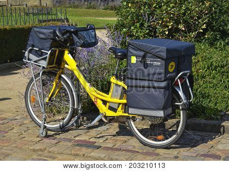 LE MANS FRANCE - AUGUST 31 2017: Yellow bicycle of a post office La Poste of French city parked on the street of Le mans. postman went to deliver the mail