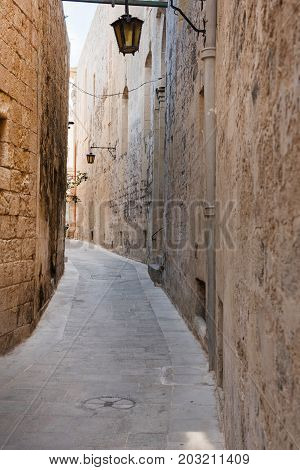 Narrow Medieval Street With Stone Houses In Mdina, Malta