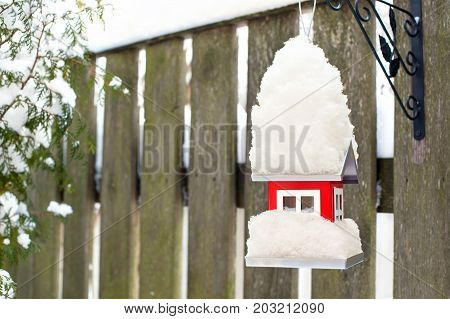 Hanging bird red metal feeder covered by snow in winter. Outdoors horizontal closeup image.
